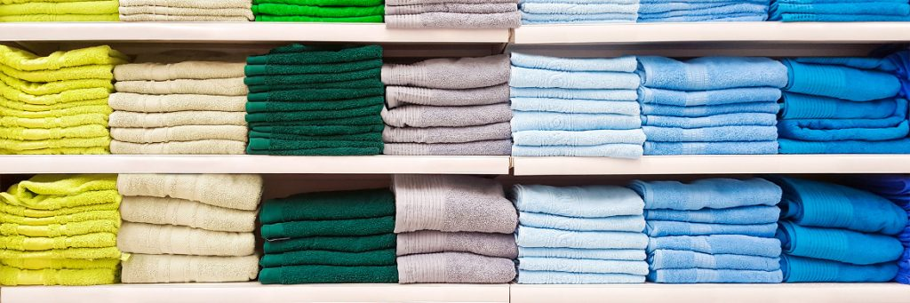 Big pile of colorful towels on shelf
